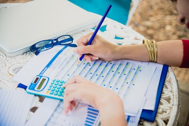 Vue de dessus de la jeune femme qui travaille à l'aide d'un ordinateur portable et de lire le rapport annuel au travail. femme d'affaires travaillant à son bureau.