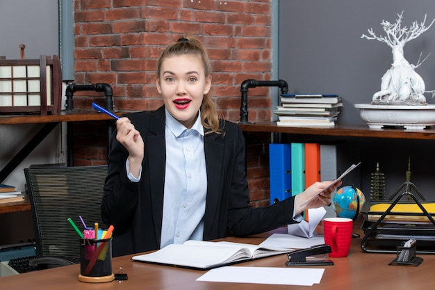 Vue de dessus d'une jeune femme surprise assise à une table et tenant un document avec un stylo de couleur bleue au bureau