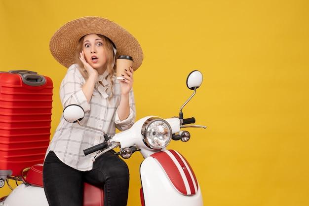 Vue de dessus de la jeune femme surprise portant chapeau et assis sur la moto et tenant le café