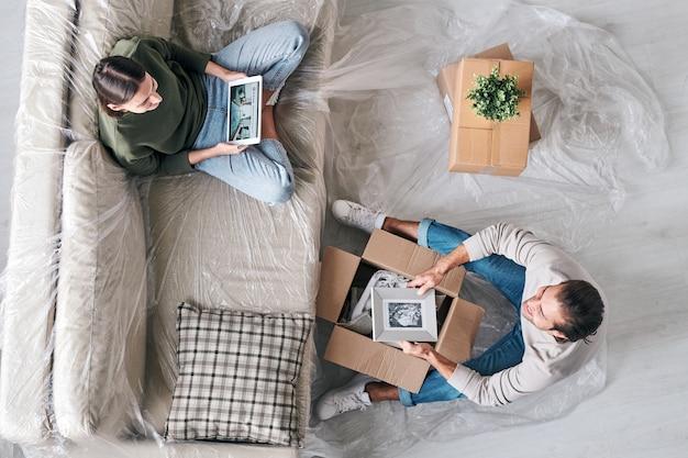 Vue de dessus de la jeune femme avec tablette et son mari avec photo dans le cadre assis en face de l'autre et bavardant dans un nouvel appartement