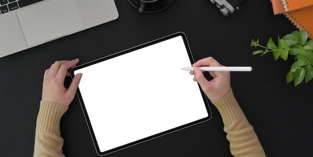 Vue de dessus de la jeune femme travaillant sur son projet avec tablette écran vide