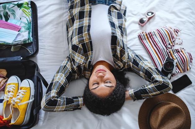 Une vue de dessus d'une jeune femme avec une valise pour des vacances à la maison, concept de coronavirus.