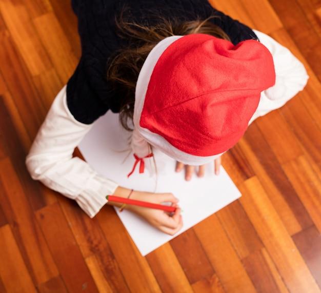 Vue de dessus d'une jeune fille à écrire une lettre