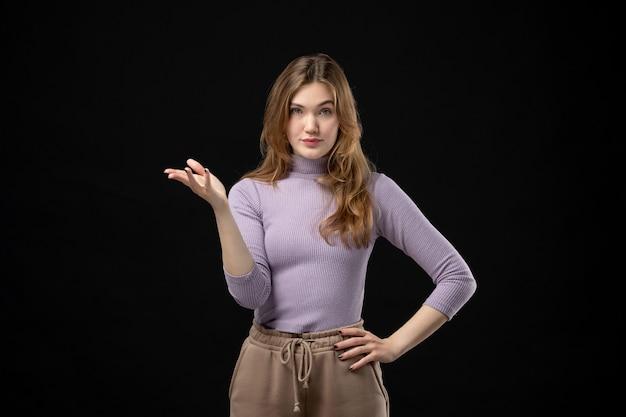 Vue de dessus d'une jeune fille réfléchie pointant quelque chose sur le côté droit dans l'obscurité