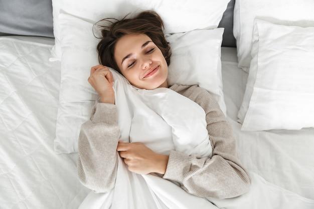 Vue de dessus d'une jeune fille souriante se détendre dans son lit le matin