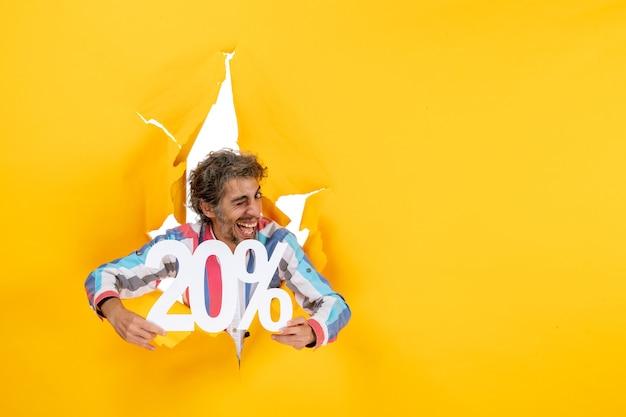 Vue de dessus d'un jeune homme drôle et souriant montrant vingt pour cent dans un trou déchiré dans du papier jaune
