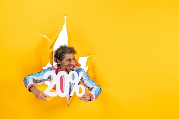 Vue de dessus d'un jeune homme émotif montrant vingt pour cent dans un trou déchiré dans du papier jaune
