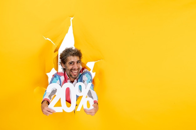 Vue de dessus d'un jeune homme heureux montrant vingt pour cent dans un trou déchiré dans du papier jaune