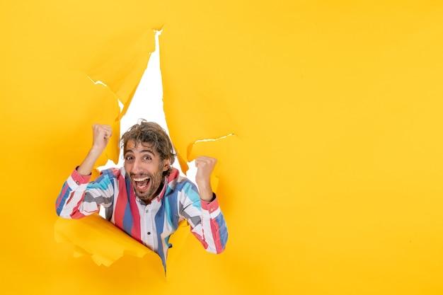 Vue de dessus d'un jeune homme heureux à travers un trou déchiré dans du papier jaune