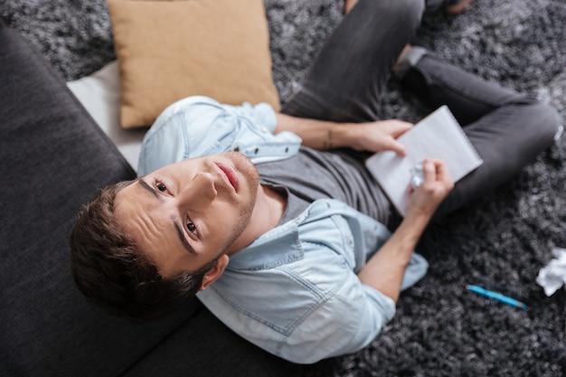 Vue de dessus d'un jeune homme réfléchi en levant et tenant le bloc-notes assis sur le tapis à la maison