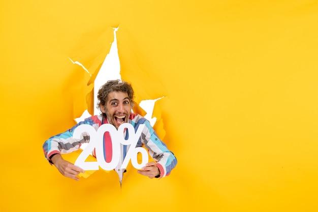 Vue de dessus d'un jeune homme souriant et heureux montrant vingt pour cent dans un trou déchiré dans du papier jaune