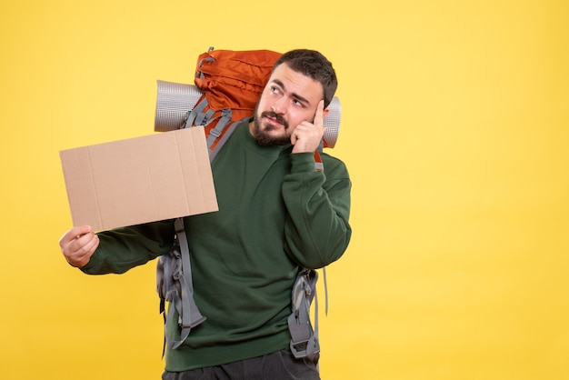 Vue de dessus d'un jeune homme de voyage pensant avec un sac à dos tenant une feuille sans écrire sur du jaune