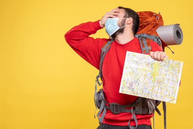 Vue de dessus d'un jeune voyageur épuisé portant un masque médical avec un sac à dos tenant une carte en jaune