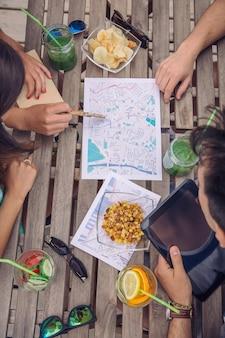 Vue de dessus de jeunes amis touristes à la recherche de cartes lors d'une pause voyageant sur une table en bois avec des boissons saines et des collations. concept de vacances et de tourisme.