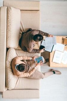 Vue de dessus de jeunes courtiers assis sur un canapé moelleux au bureau et travaillant avec des informations financières tout en regardant à travers des documents