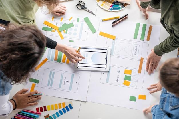 Vue de dessus de jeunes développeurs de logiciels professionnels créatifs discutant des croquis et des schémas de nouvelles applications mobiles lors d'une réunion de travail