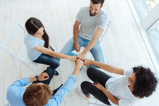 Vue de dessus de jeunes heureux heureux assis dans le cercle et souriant tout en tenant leurs poings ensemble