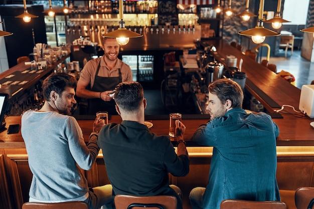Vue de dessus de jeunes hommes détendus en vêtements décontractés buvant de la bière assis dans le pub