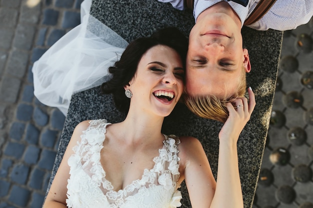 Vue de dessus de jeunes mariés heureux couché