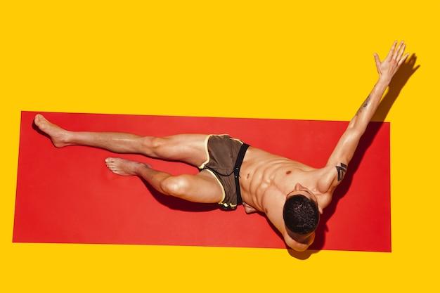 Vue de dessus de jeunes modèles masculins de race blanche reposant sur une station balnéaire