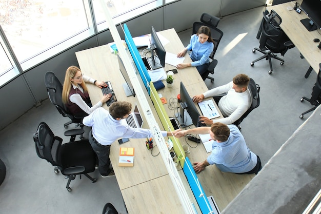Vue de dessus de jeunes partenaires commerciaux se serrant la main au bureau. concentrez-vous sur la poignée de main.