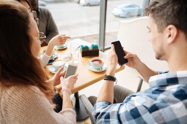 Vue de dessus des jeunes utilisant leurs smartphones assis au café pendant la pause déjeuner.