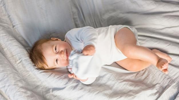 Vue de dessus joli bébé blonde dans un lit blanc