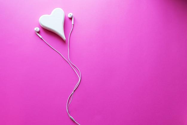 Vue de dessus joli gros plan d'écouteurs blancs sur fond de texture en plastique rose pastel.