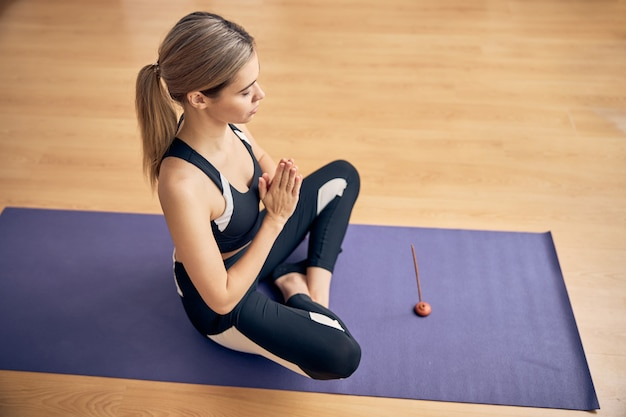 Vue de dessus d'une jolie dame utilisant un bâton aromatique tout en faisant des exercices d'étirement sur un tapis de sol dans une salle de cours de yoga