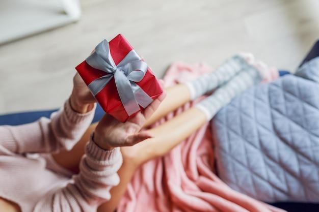 Vue de dessus sur jolie femme tenant une boîte-cadeau, assise sur un canapé à la maison. photo douce. concept de vacances.