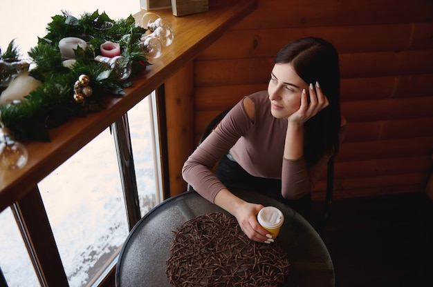Vue de dessus d'une jolie femme tenant une tasse de papier à emporter avec boisson chaude, assise au café en bois et regardant par la fenêtre. belle décoration de noël sur la planche de bois à côté de la fenêtre