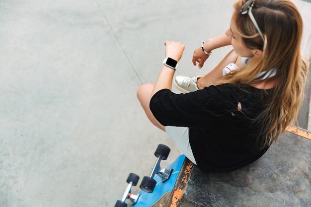 Vue de dessus d'une jolie jeune adolescente assise au skatepark avec un longboard, vérifiant sa montre intelligente