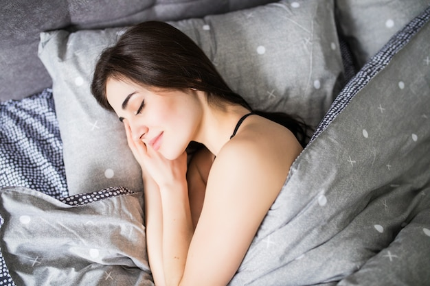Vue de dessus de la jolie jeune femme dormant bien dans son lit, étreignant un oreiller blanc doux. adolescente au repos, bonne nuit de sommeil concept.