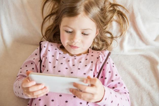 Vue de dessus de la jolie petite fille avec tablette à la main