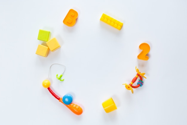 Vue de dessus de jouets pour bébés de différentes couleurs sur fond blanc, mise à plat