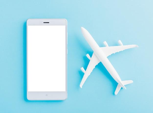 Vue de dessus de la journée mondiale du tourisme d'un avion modèle jouet minimal et d'un écran vierge de smartphone
