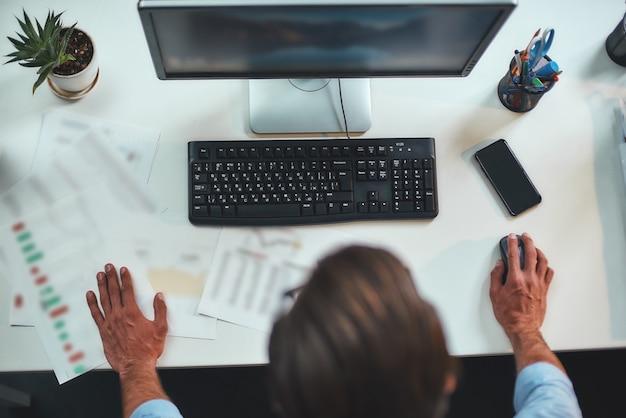 Vue de dessus d'une journée de travail occupée d'un homme d'affaires travaillant sur l'ordinateur en se tenant debout