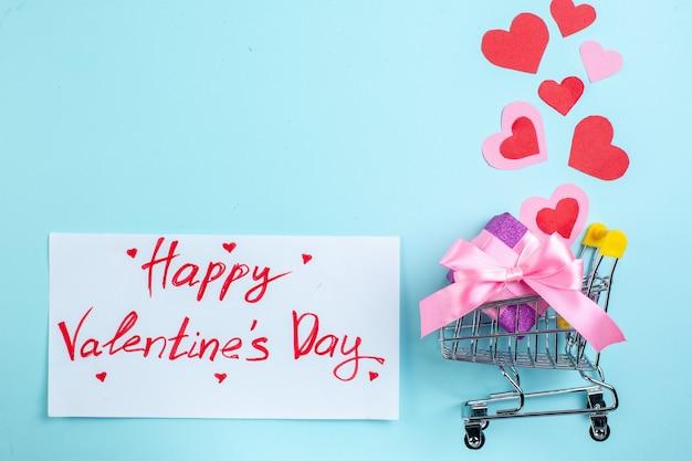 Vue de dessus joyeuse saint valentin écrit sur papier mini chariot coeurs rouges et roses avec cadeau sur fond bleu avec espace libre