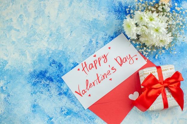 Vue de dessus joyeuse saint valentin écrite sur la lettre fleurs cadeau enveloppe rouge sur fond bleu espace libre