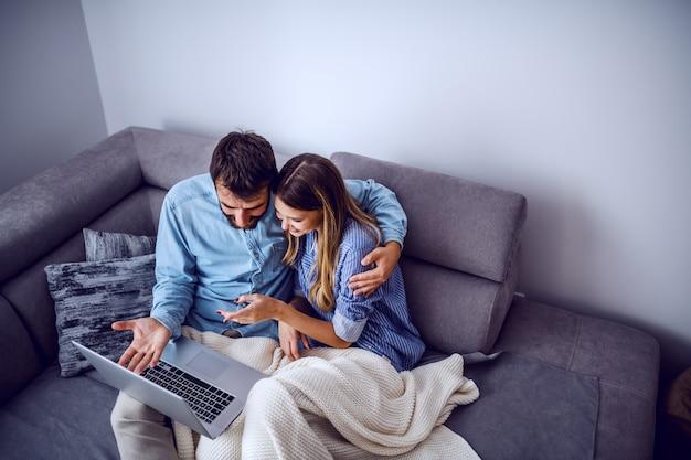 Vue de dessus de joyeux couple caucasien mignon assis sur un canapé recouvert d'une couverture et à l'aide d'un ordinateur portable pour surfer sur internet. intérieur du salon.