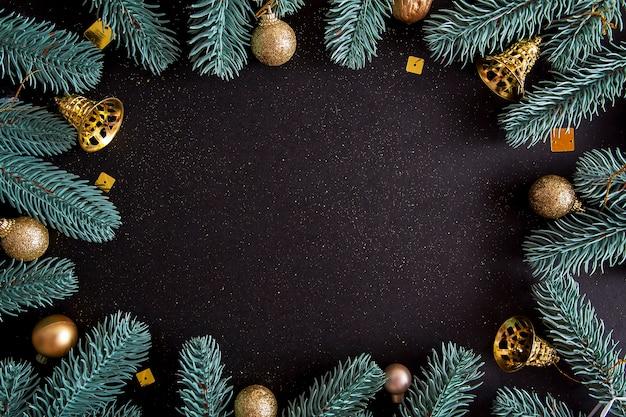 Vue de dessus joyeux noël fond noir décoré de branches d'arbres de noël de bonne année et de boules avec espace copie. concept d'amusement festif de décoration de carte de vacances d'hiver, plat poser.