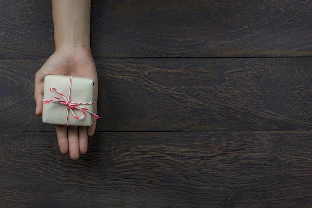 Vue de dessus joyeux nouvel an festival ou anniversaire et joyeux noël fond concept.mains tenant le petit cadeau. objet sur le bois rustique brun moderne à la maison bureau avec espace copie.