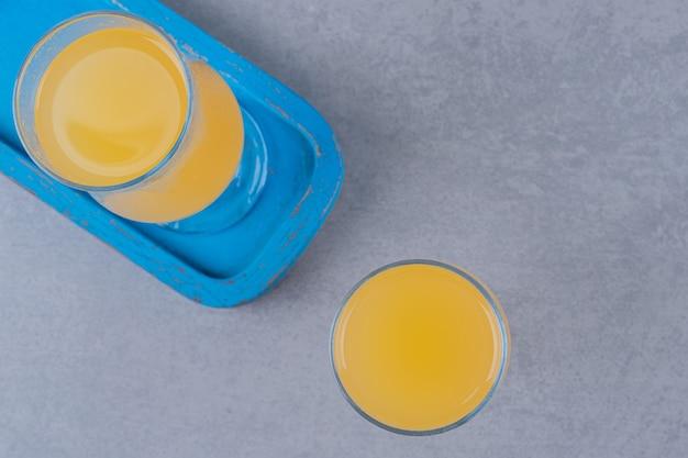 Vue de dessus des jus d'orange frais sur planche de bois bleue