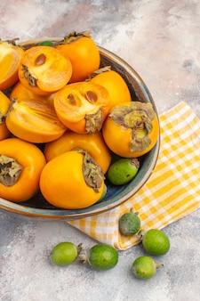 Vue de dessus des kakis frais dans un bol en bois serviette de cuisine jaune feykhoas sur fond nu