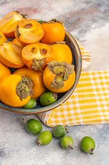 Vue de dessus des kakis frais dans un bol serviette de cuisine jaune feykhoas sur fond nu