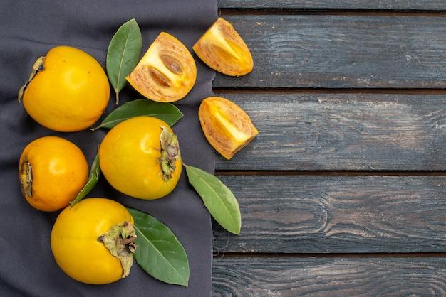 Vue de dessus kakis sucrés frais sur une table rustique en bois, fruits moelleux