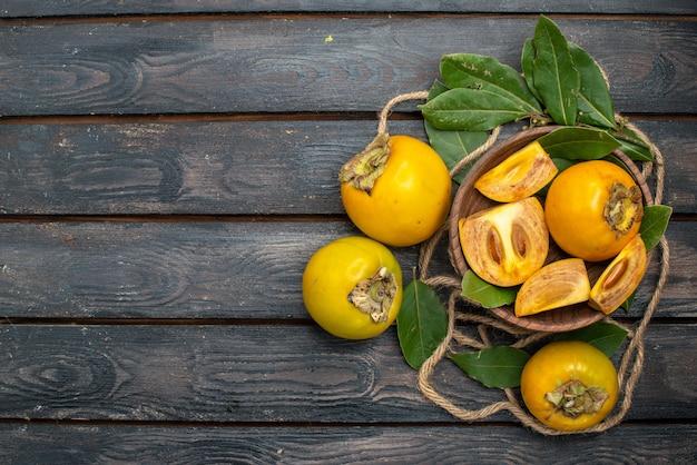 Vue de dessus kakis sucrés frais sur table rustique en bois, goûter les fruits mûrs