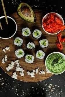 Vue de dessus kappa maki roule sur un support avec du gingembre sauce soja avacado riz bouilli et wasabi