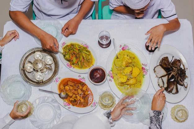 Vue de dessus de ketupat lebaran plat de célébration traditionnel indonésien de gâteau de riz avec plusieurs plats d'accompagnement servis sur la table pendant l'eid mubarak