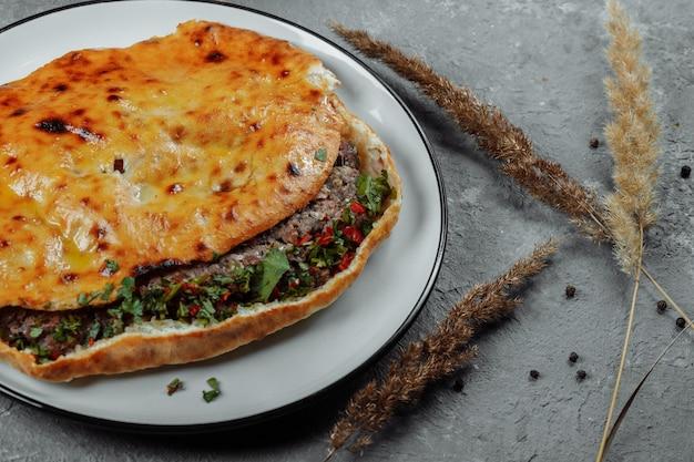 Vue de dessus sur le khachapuri géorgien avec de l'agneau et des piments sur la table en bois.